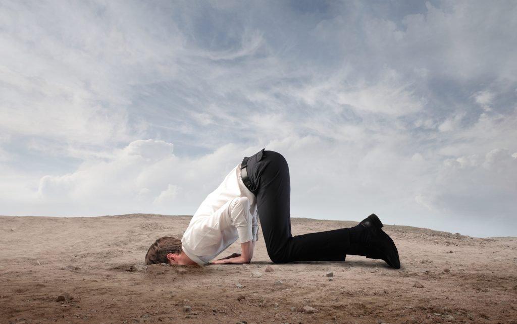 devekuşu gibi başını kuma gömen adam